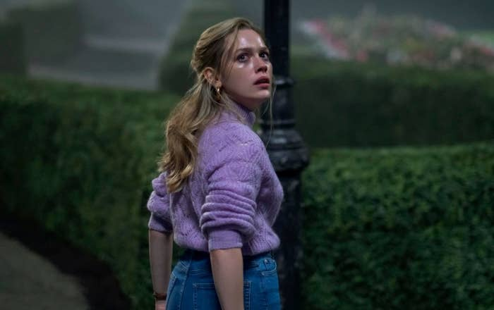 Still from the Haunting of Bly Manor: Dani stands in the garden at night, sweaty and upset, looking back towards the house