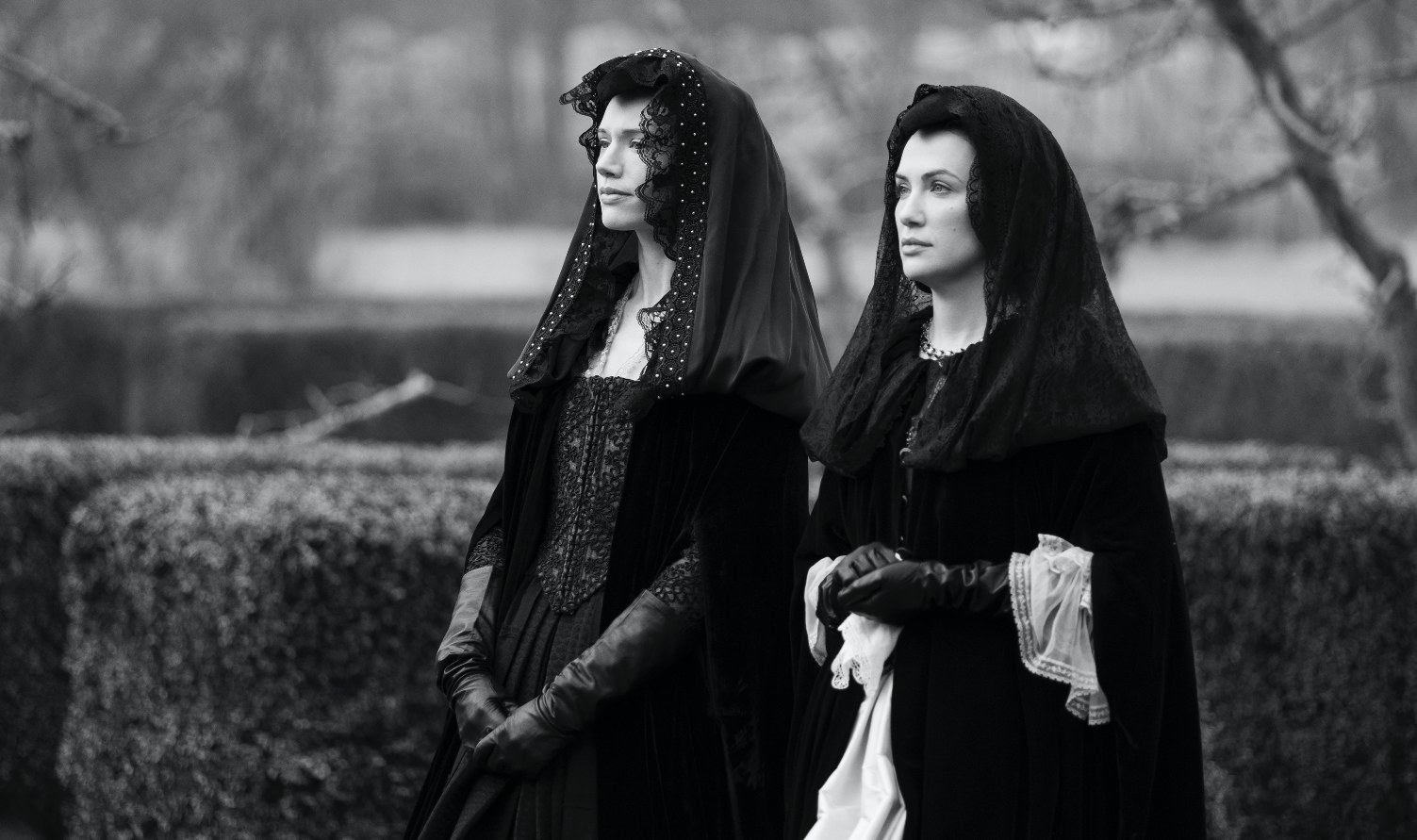 The Haunting of Bly Manor still: in black and white, Perdita and Viola sisters stand in period clothes symbolizing mourning