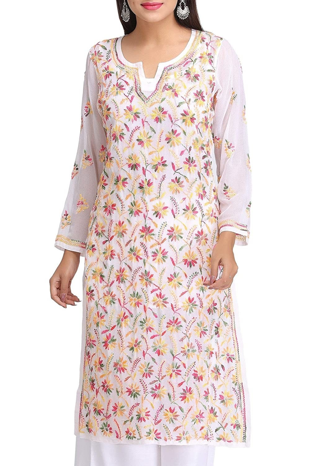 A person wearing a white kurta with pink, yellow and green chikankari on it.