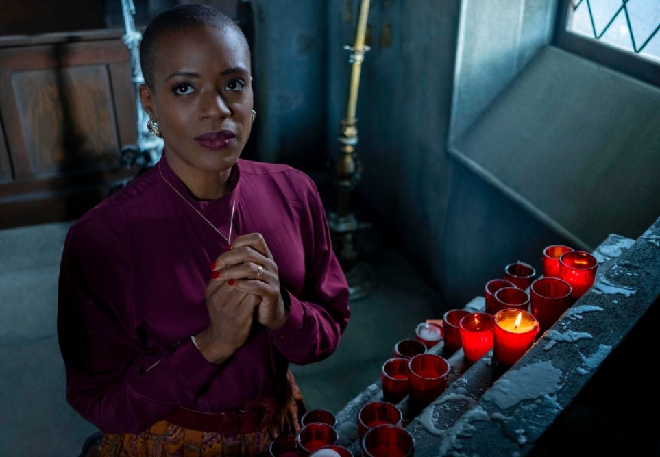 Still from The Haunting of Bly Manor: Hannah prays in front of lit candles at the chapel