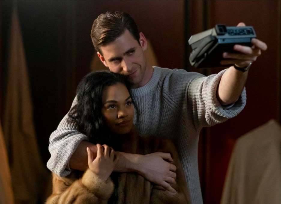 The Haunting of Bly Manor still: Peter Quint wraps one arm around Rebecca Jessel and holds up a polaroid camera focused on them with his other arm