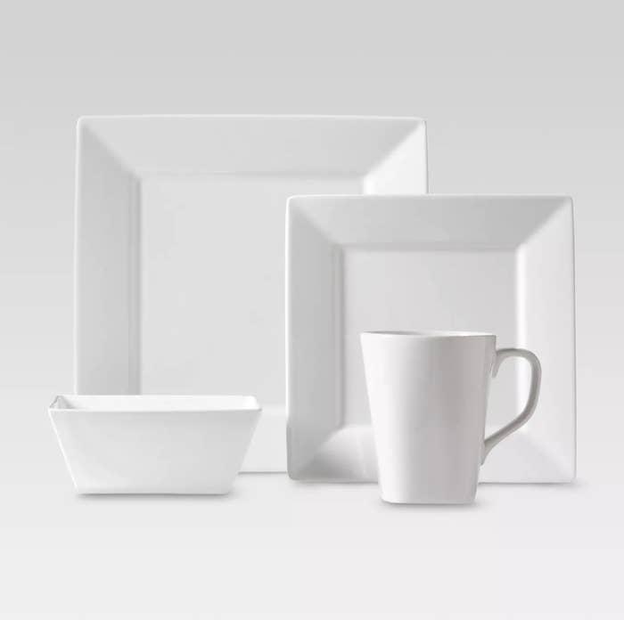 Two white square plates, a white square bowl, and a white mug