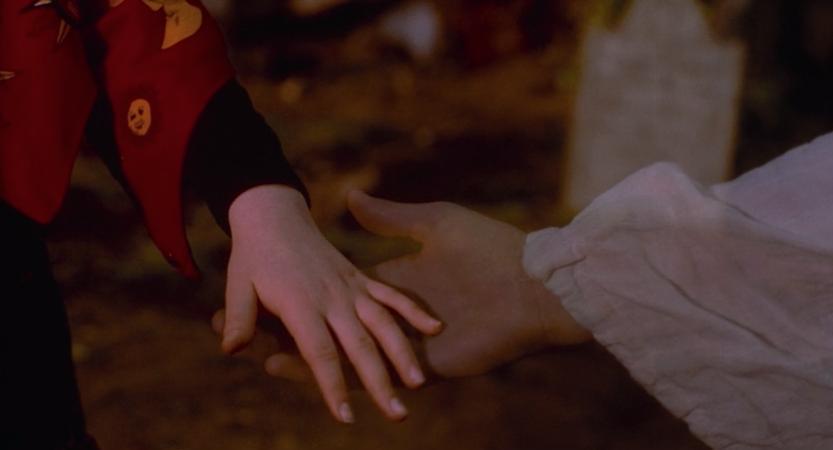 Dani's human hand touching Thackery's ghost hand.