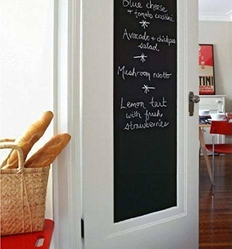 Chalkboard decal in a kitchen with some names of dishes written on it.