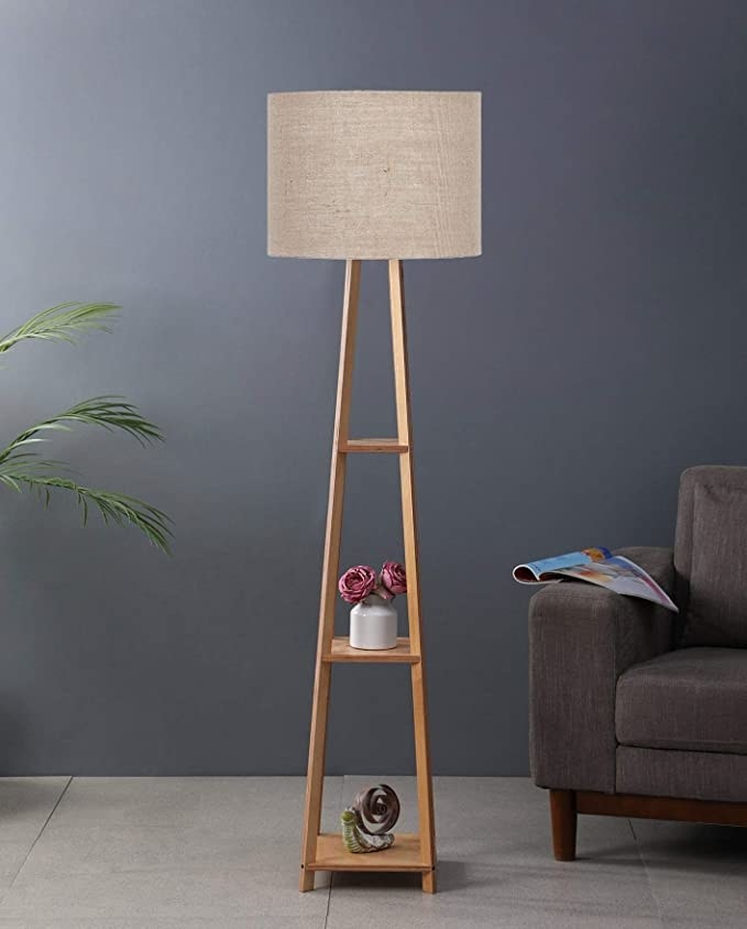 Tall wooden lamp with a white lamp shade.