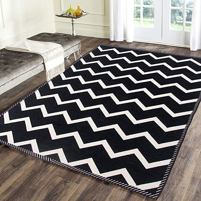 Black rug with a white zigzag pattern.