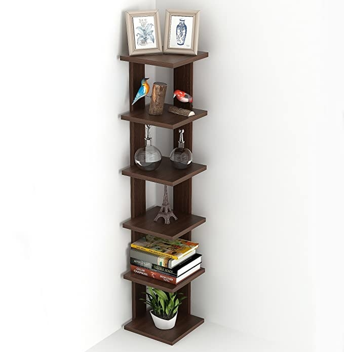6 layer corner shelf with books and plants on it.