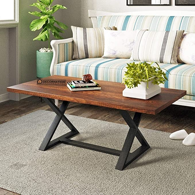 Coffee table with a wooden finish top and black legs.
