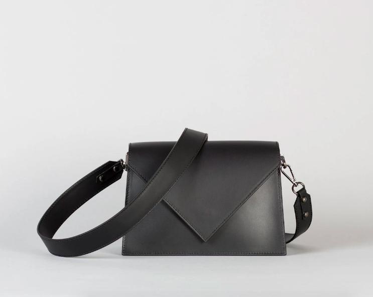 Black handbag with crossbody strap and triangular flap