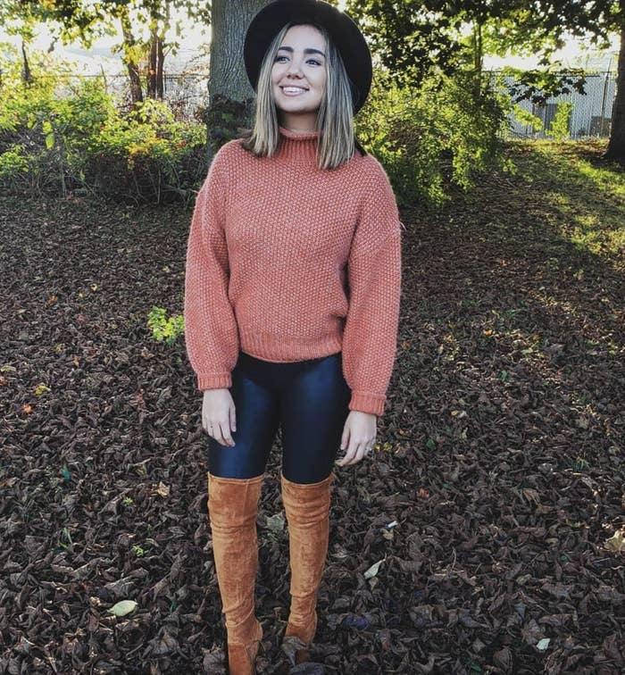 reviewer wearing the orange sweater