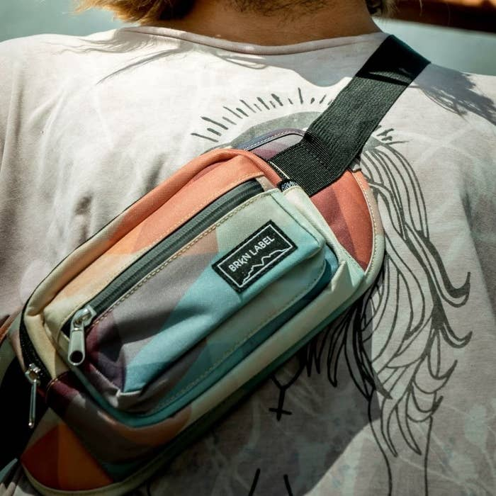 A close up of a person wearing the belt bag slung across their shoulder