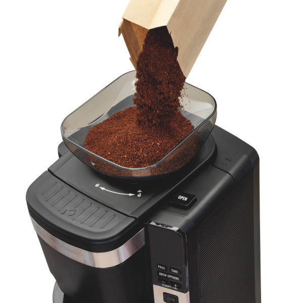 person pouring coffee grounds on the top of the coffee maker