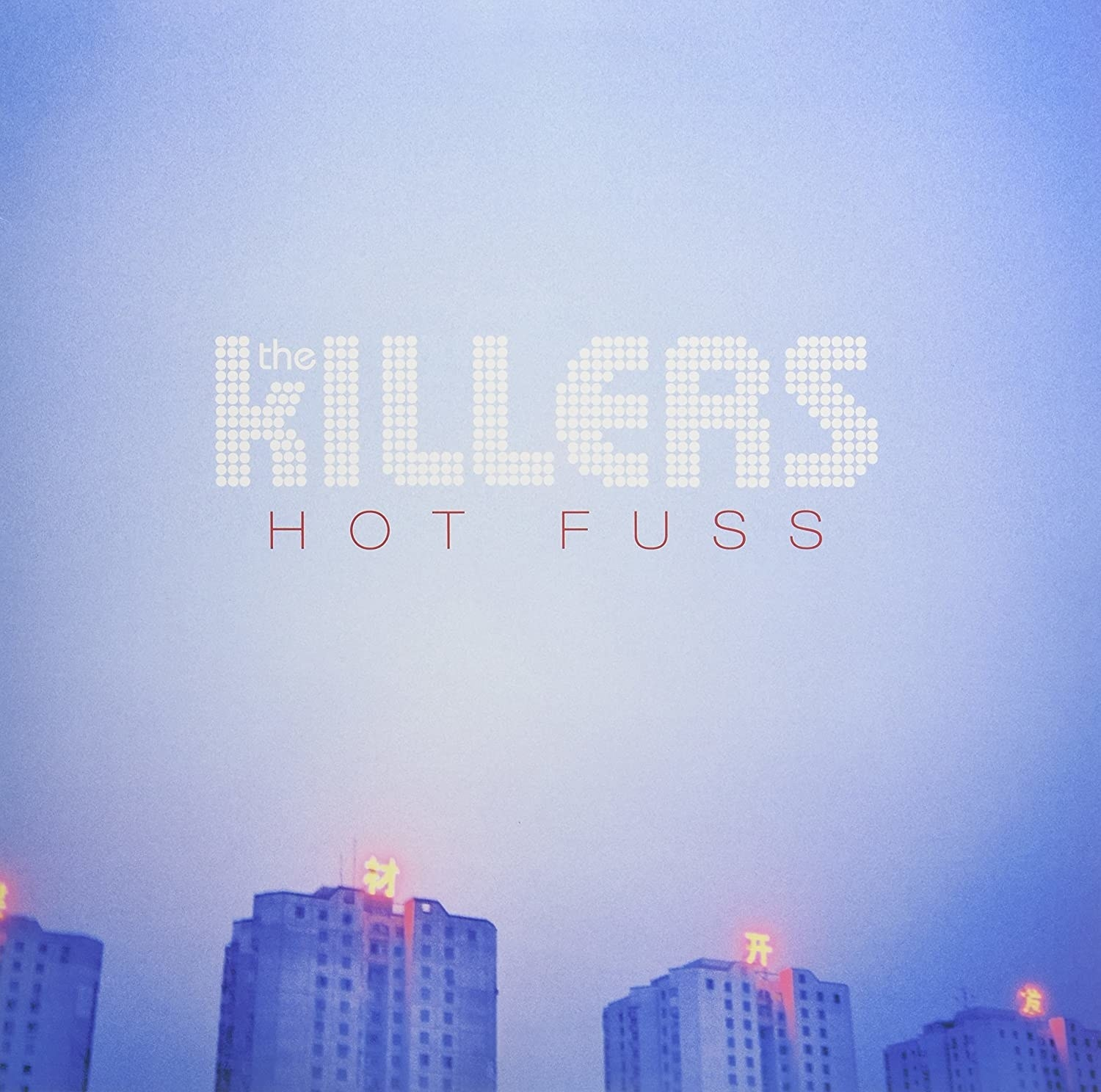 album cover of The Killers' Hot Fuss showing a hazy blue sky over high-rise buildings.