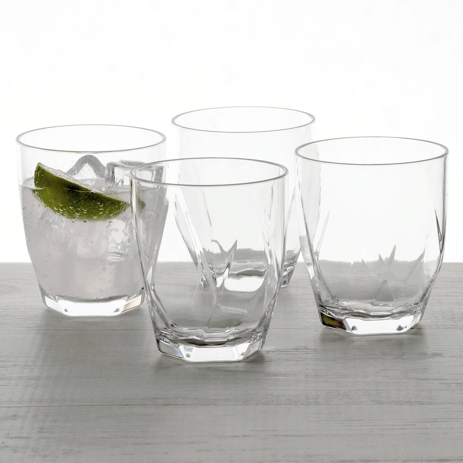 four old fashioned glasses with a vodka soda in one of them