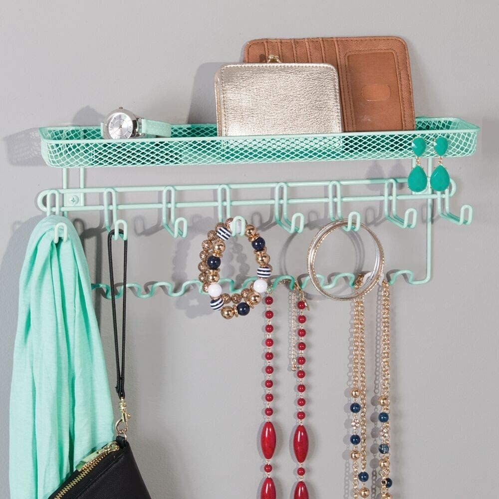 The mint green mDesign Closet Wall Mount Men's Accessory Storage Organizer Rack holding jewelry, a scarf, and a purse