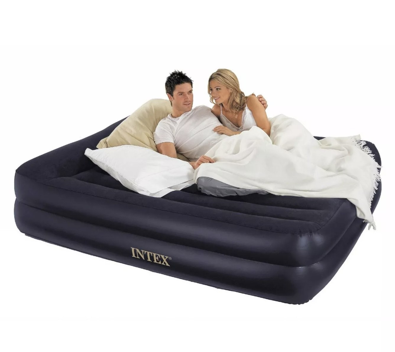 Two models laying on top of a black inflatable mattress with pillows and a blanket