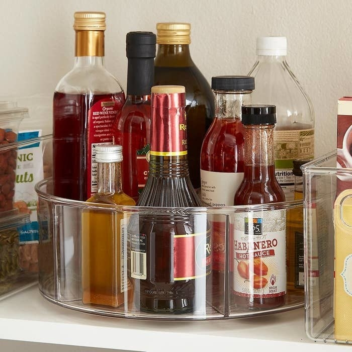 The divided Lazy Susan filled with various condiments inside someone's cabinet