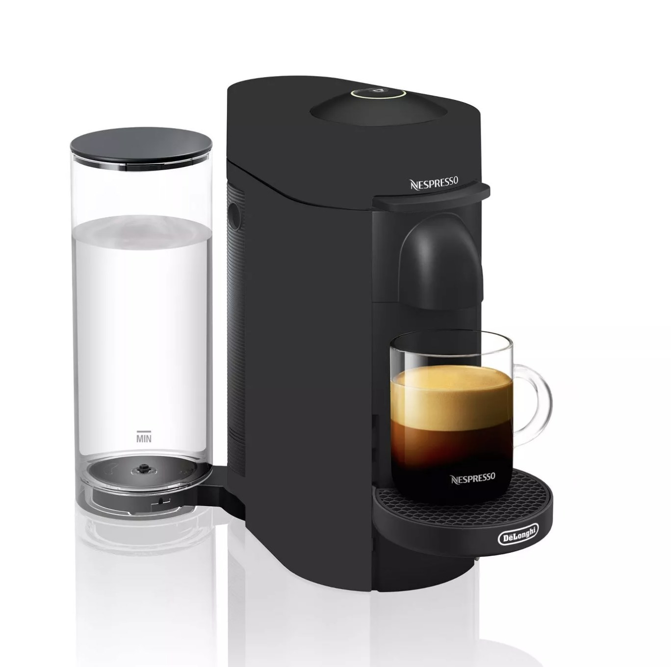 A black expresso machine with a glass mug on the base with expresso inside and a white container holding water behind it