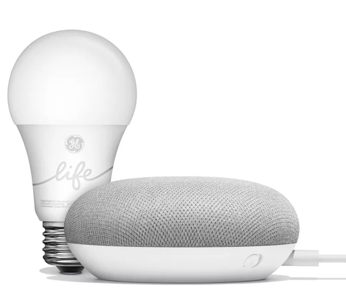 A white Google Home device next to a smart lightbulb