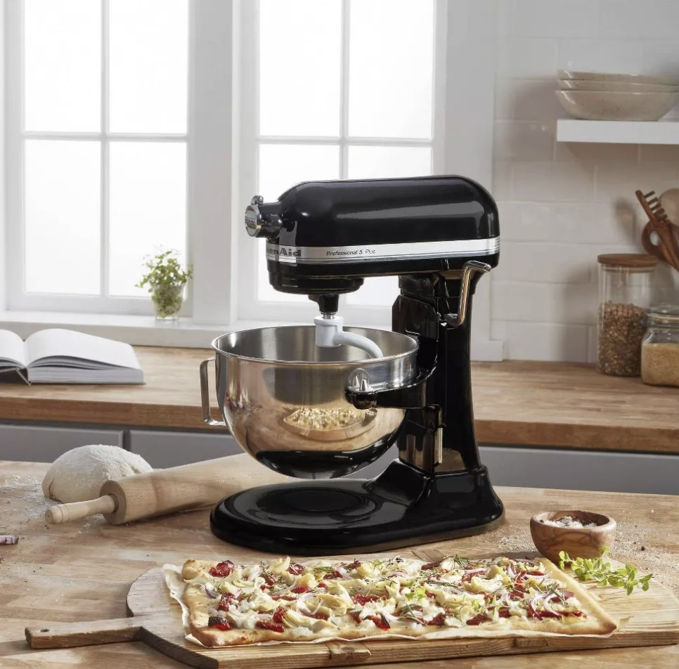 A black KitchenAid stand mixer in a kitchen next to a flatbread pizza