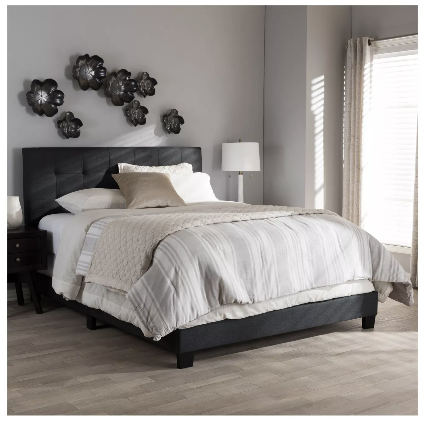 A dark grey fabric bed frame under a mattress with comforter in a bedroom