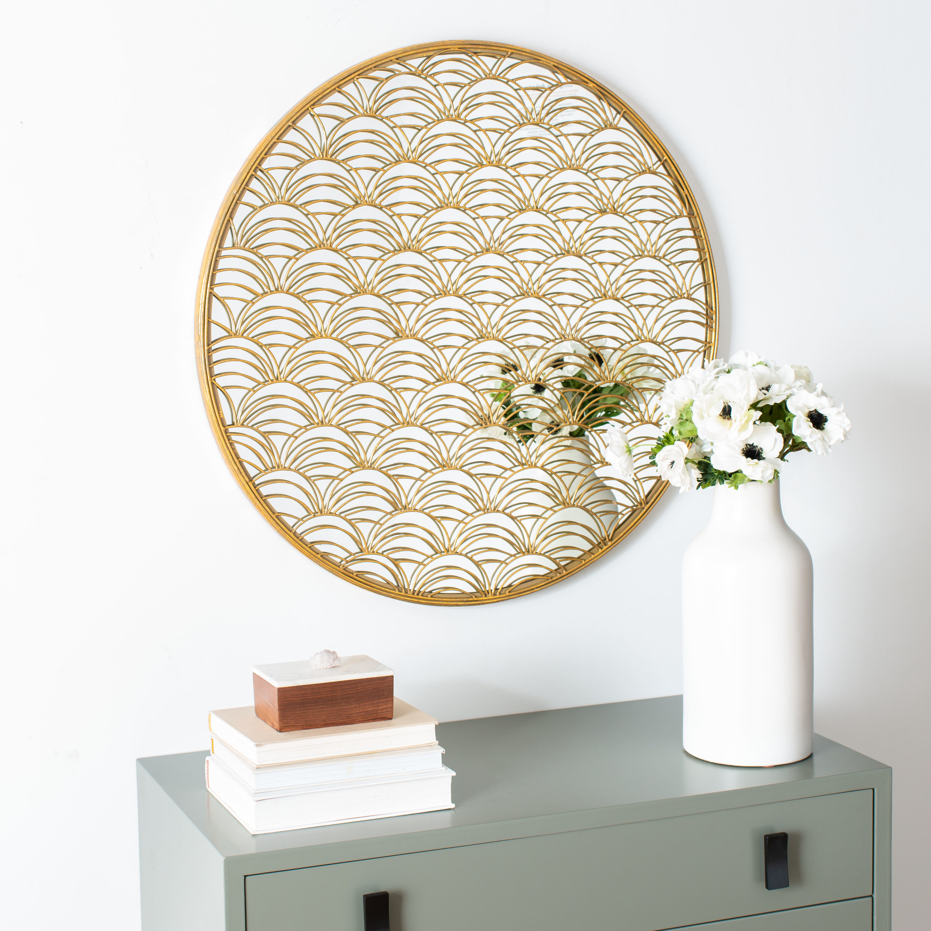round mirror with a gold foil design hung on a wall over a mint green dresser