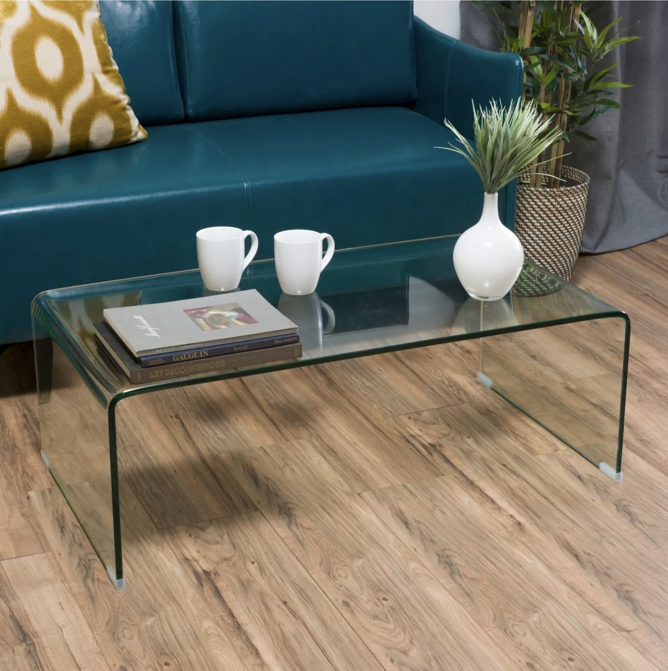 A rectangle glass coffee table sits in front of a blue couch in a living room with decor on top of it
