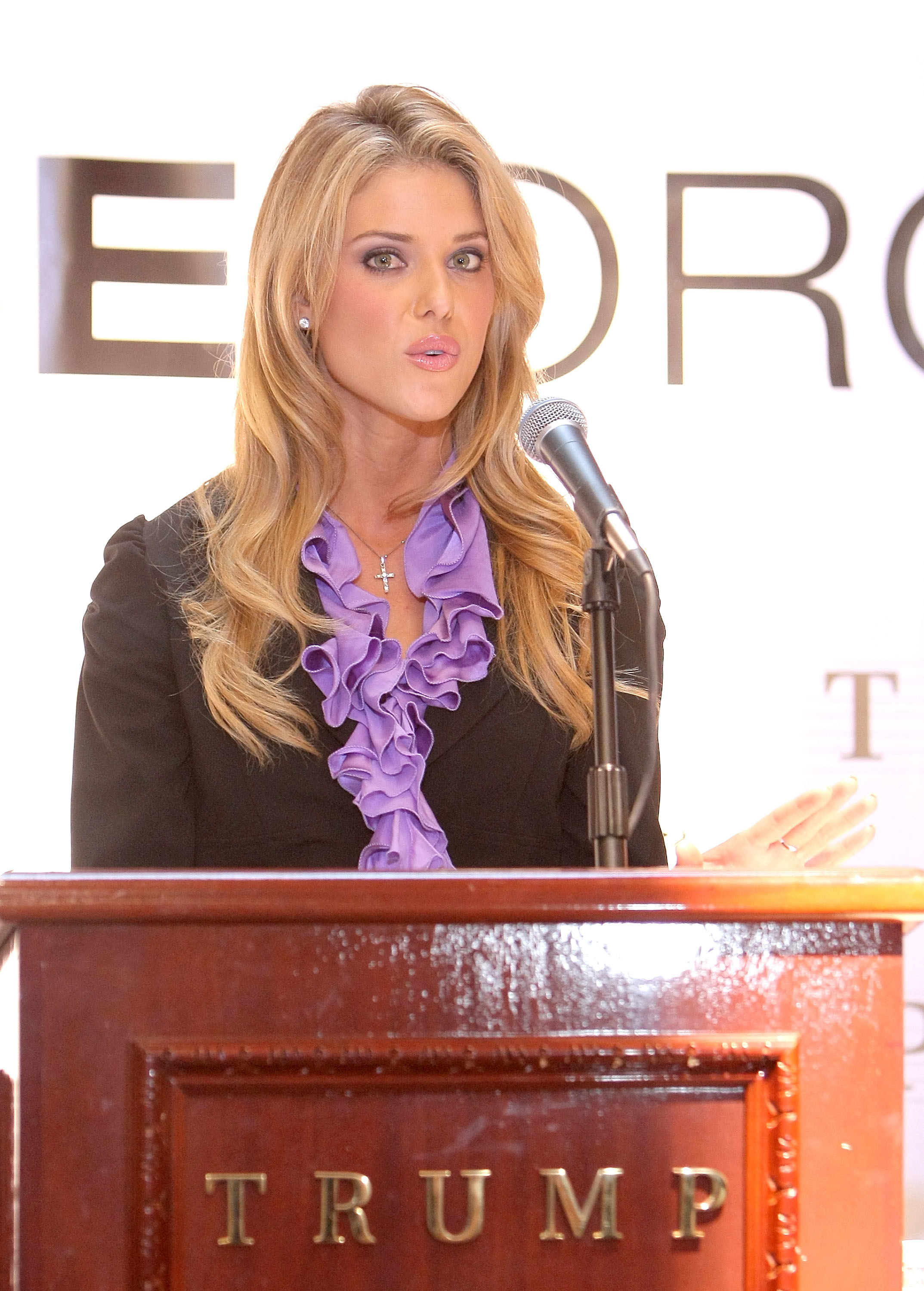 Carrie speaking at a press conference at a podium featuring Trump's name
