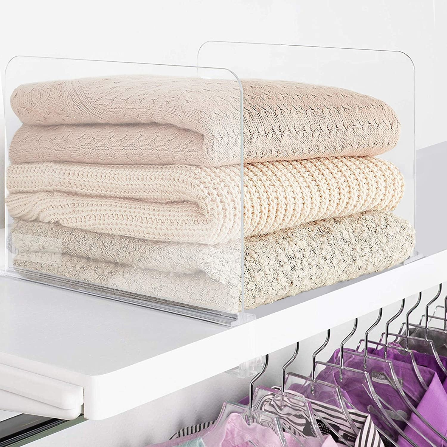 clear dividers holding up sweaters on a shelf