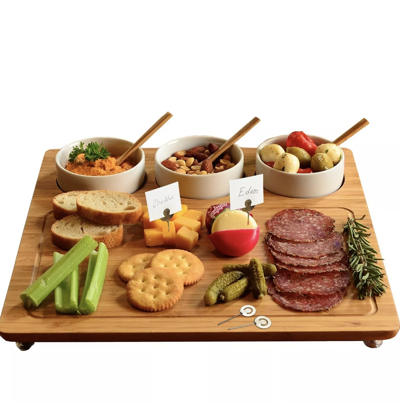 A bamboo cheese board with a variety of snacks on top and three bowls with assorted dips and spoons