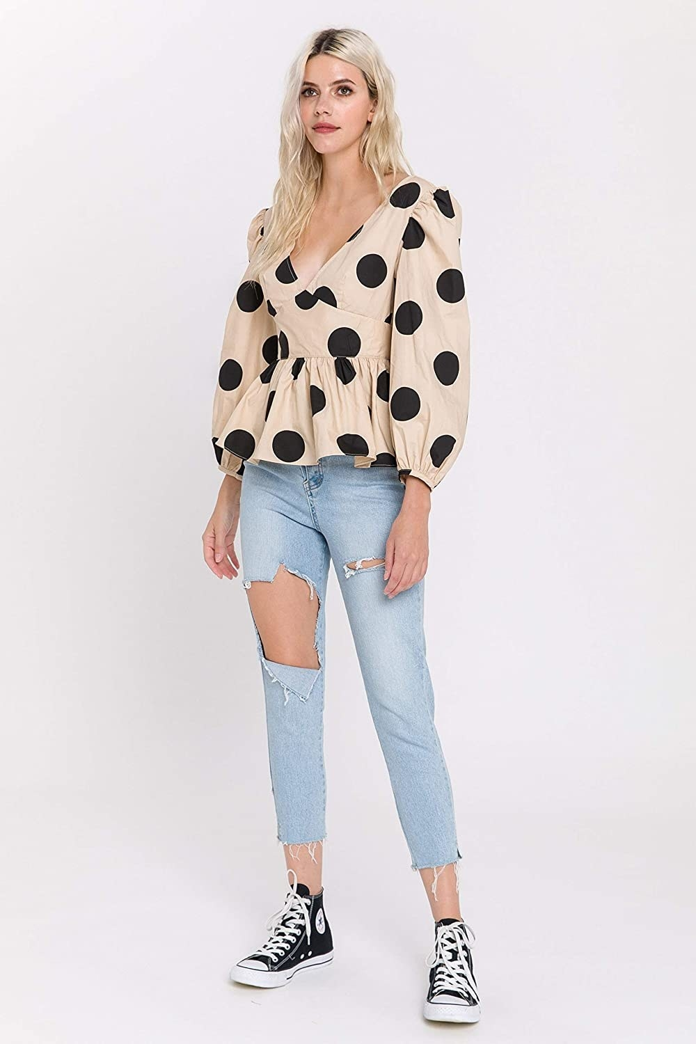 model wearing tan V-neck top with black polka dots