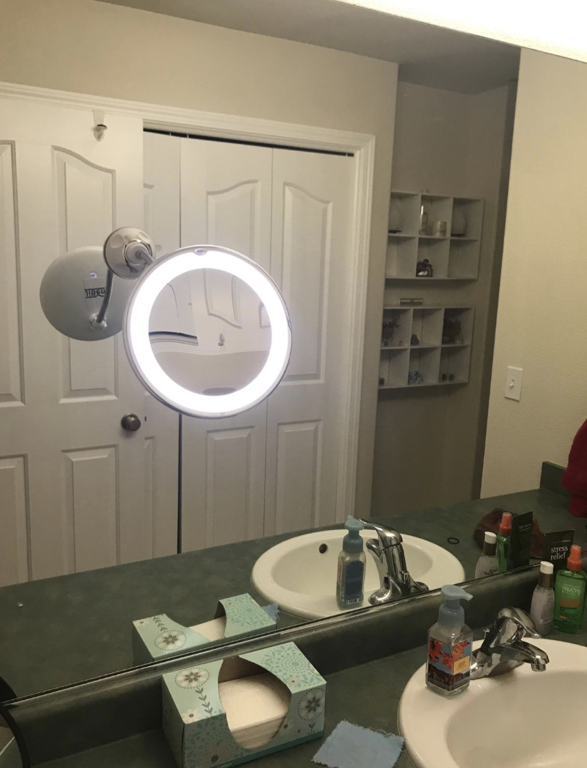 Reviewer image of a lit circular gooseneck mirror attached to the bathroom mirror