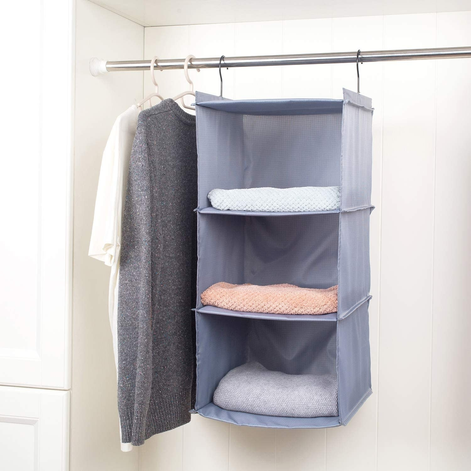 A three shelf hanging organizer in a closet with towels in it