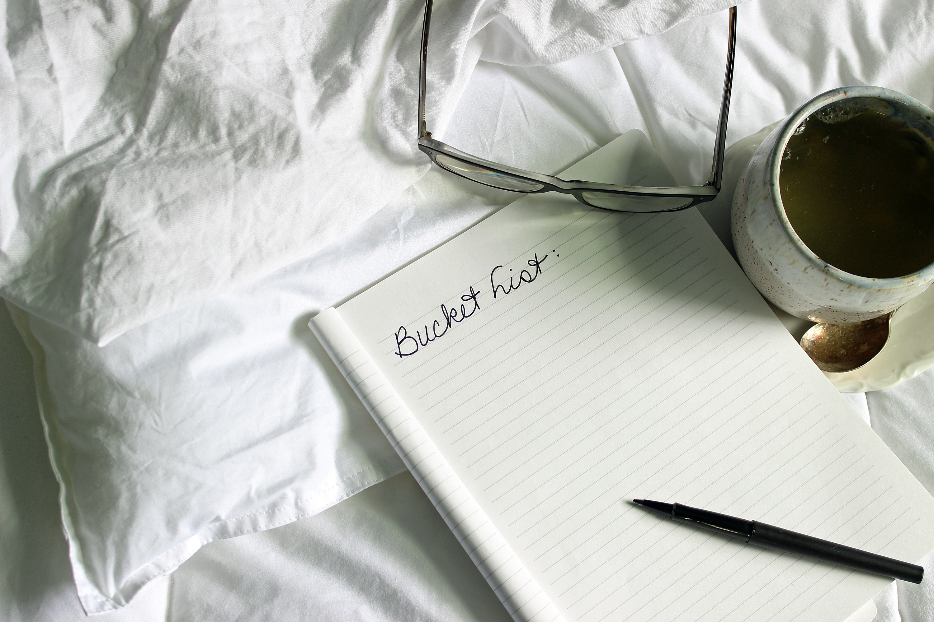 Photo of notepad on top of bed and pillow, with bucket-list written on one page with a cup of coffee to the right next to a pair of glasses and a pen on the lower corner