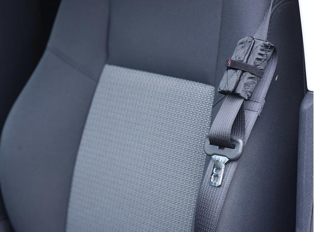 A black padded adjuster installed on a seatbelt