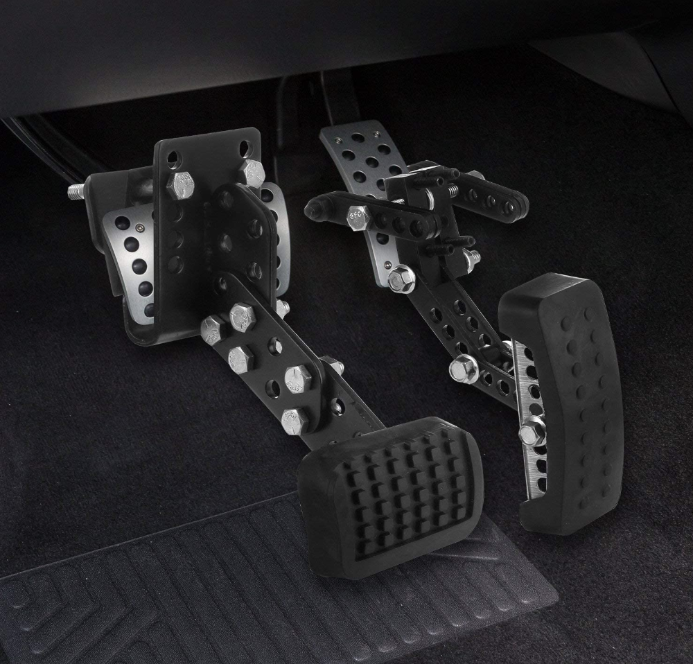 A set of black pedal extenders on the brakes and pedal of a car