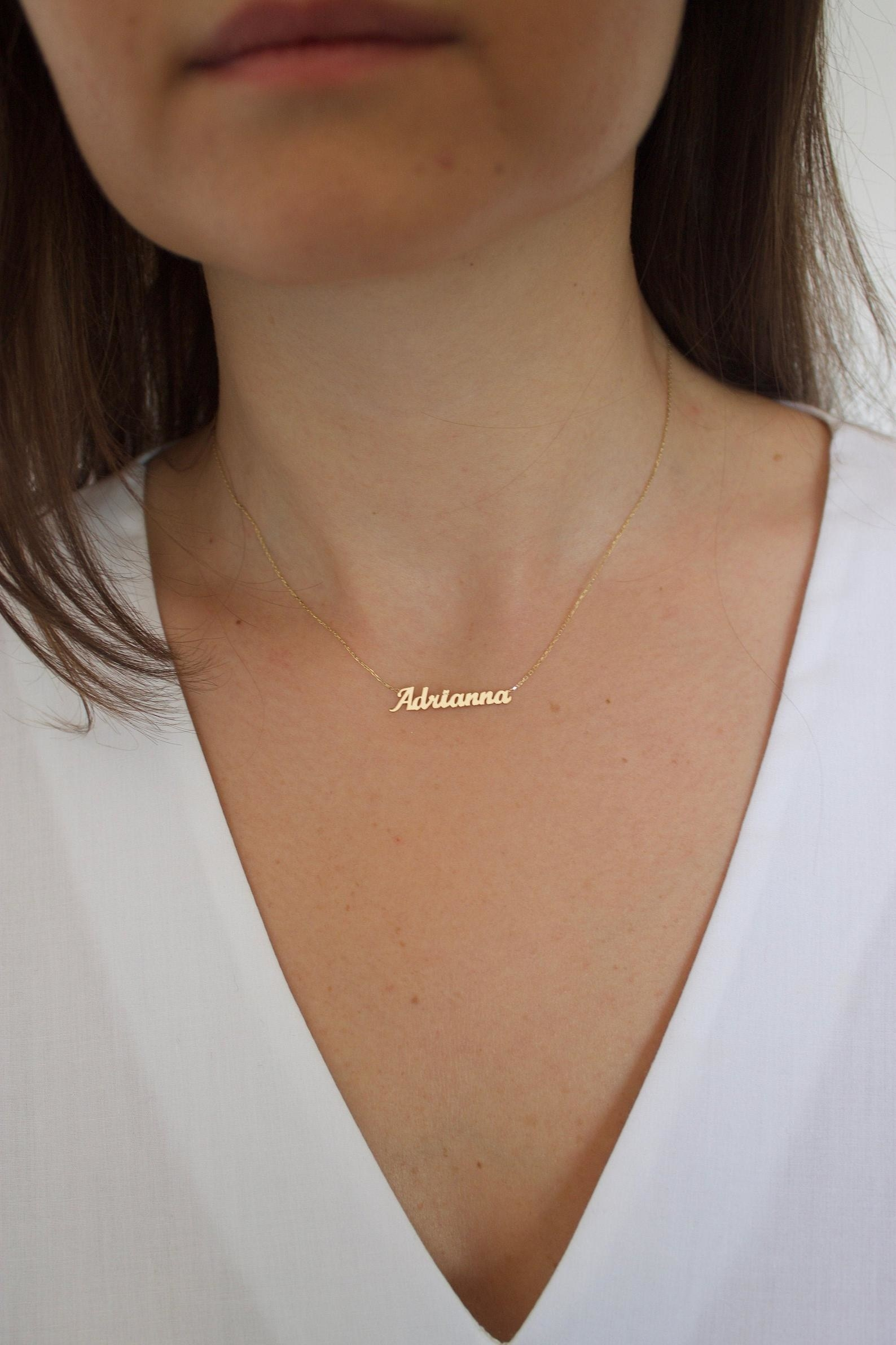"""A person with a dainty gold necklace with the name """"Adrianna"""" on it"""