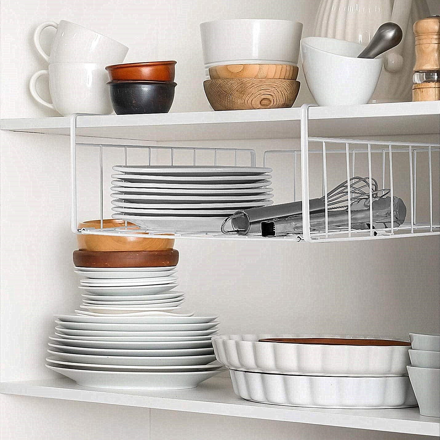 A white wire rack organizer under a shelf with plates on it