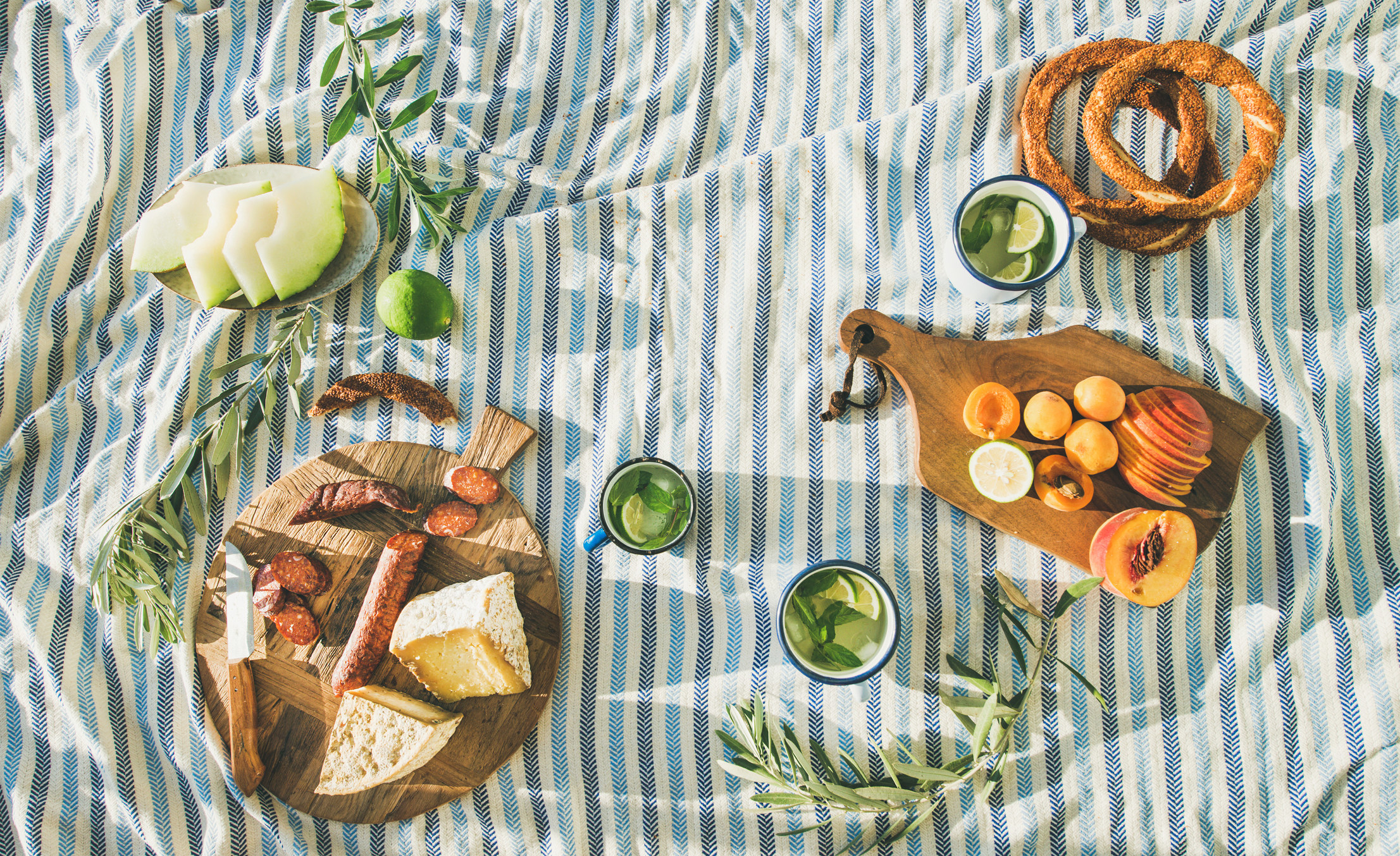 summer picnic with blue, white and navy striped blanket under three small platters of fruits with cheese, peaches, pretzels, lime and another small plate with a side of fruit