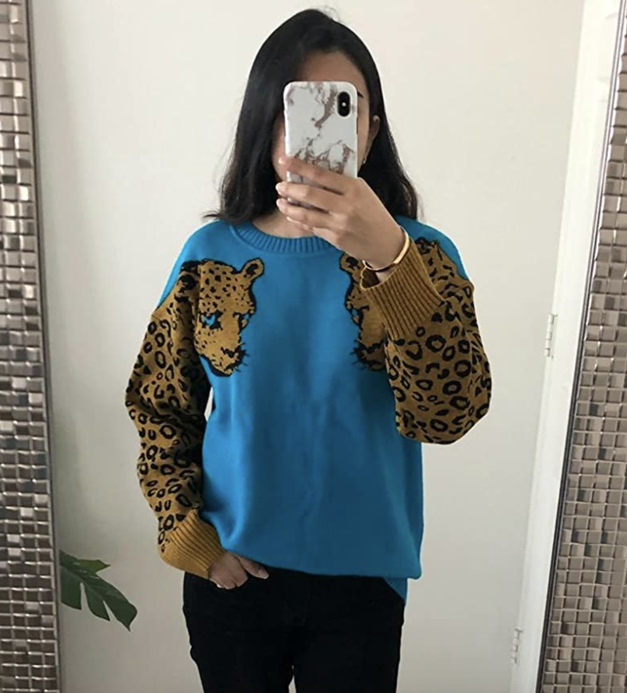 reviewer wearing the blue sweater with leopard illustration on sleeves
