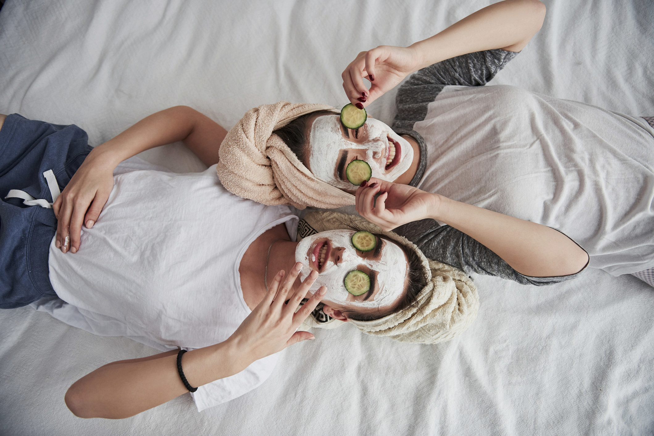 Photo of two women doing their skincare routine with a spa treatment, they both have a mask on with cucumbers on their eyes, one woman is smiling while the other is resting with her mask on, they are both wearing casual clothing while on a white bed