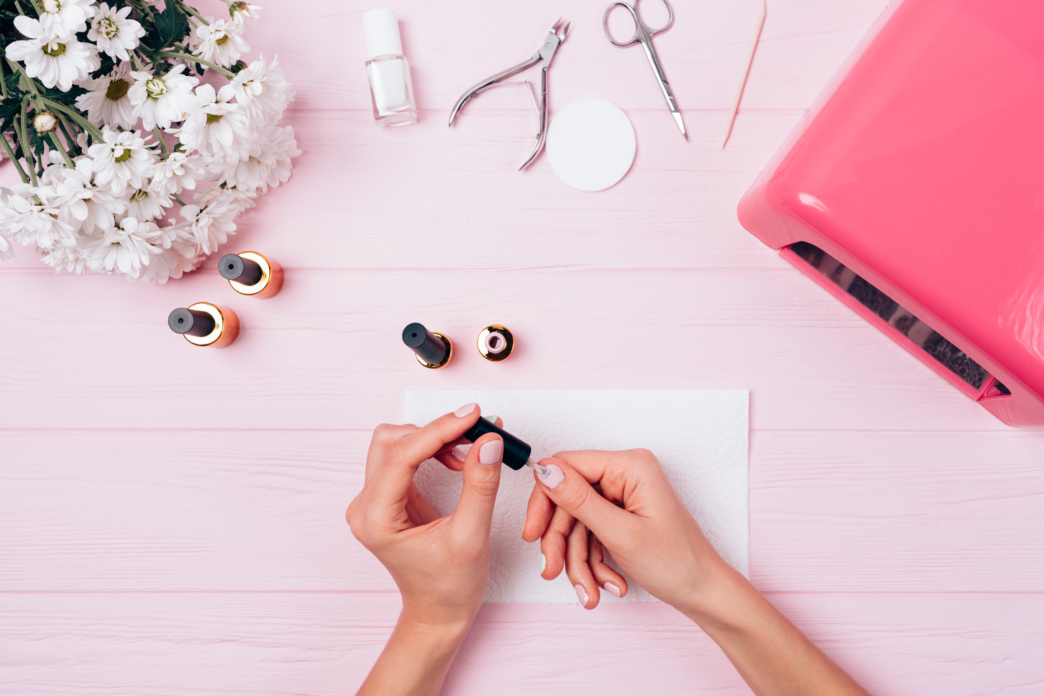 photo of someone painting their nails a light pink color on top of a light pink wooden table, on the table is also a manicure set and additional nail polish with white flowers on the top left and a uv gel monitor on the right side