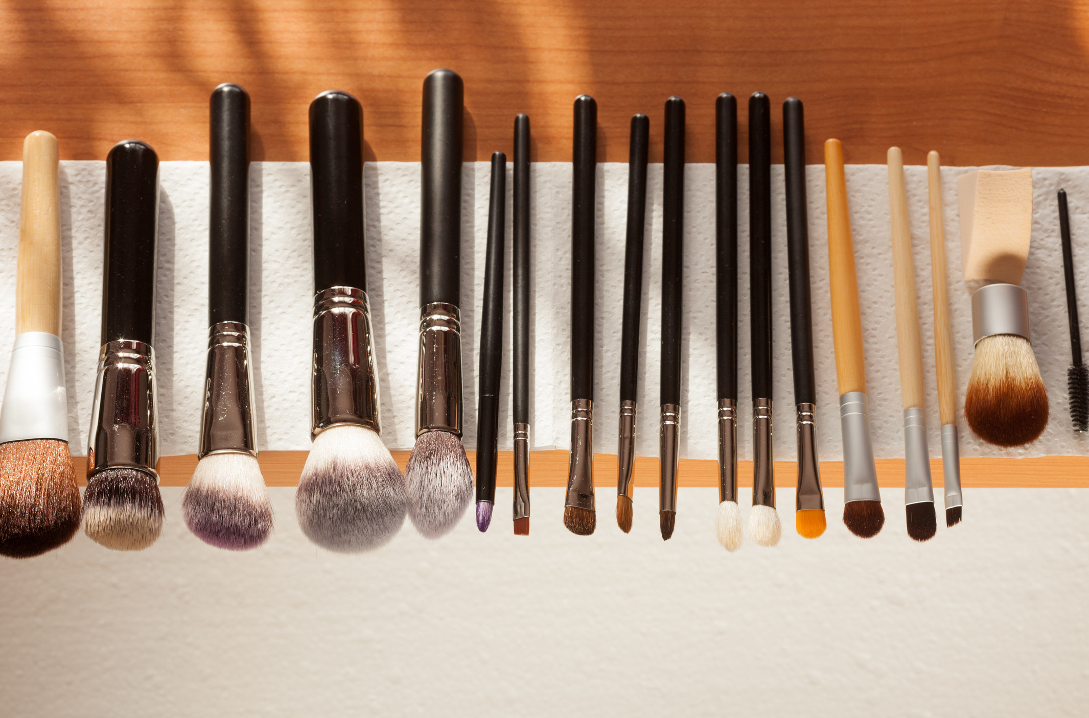 photo showing a row of cosmetic brushes that are being dried off on top of white piece of napkin after being cleaned