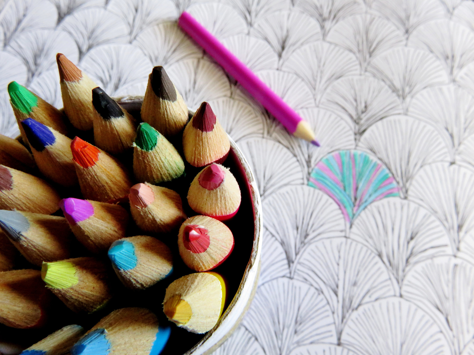 photo of coloring pencils in a can on the left corner while the can is on top of a table to draw on, in the middle is a pink pencil that has already colored in one portion of the table