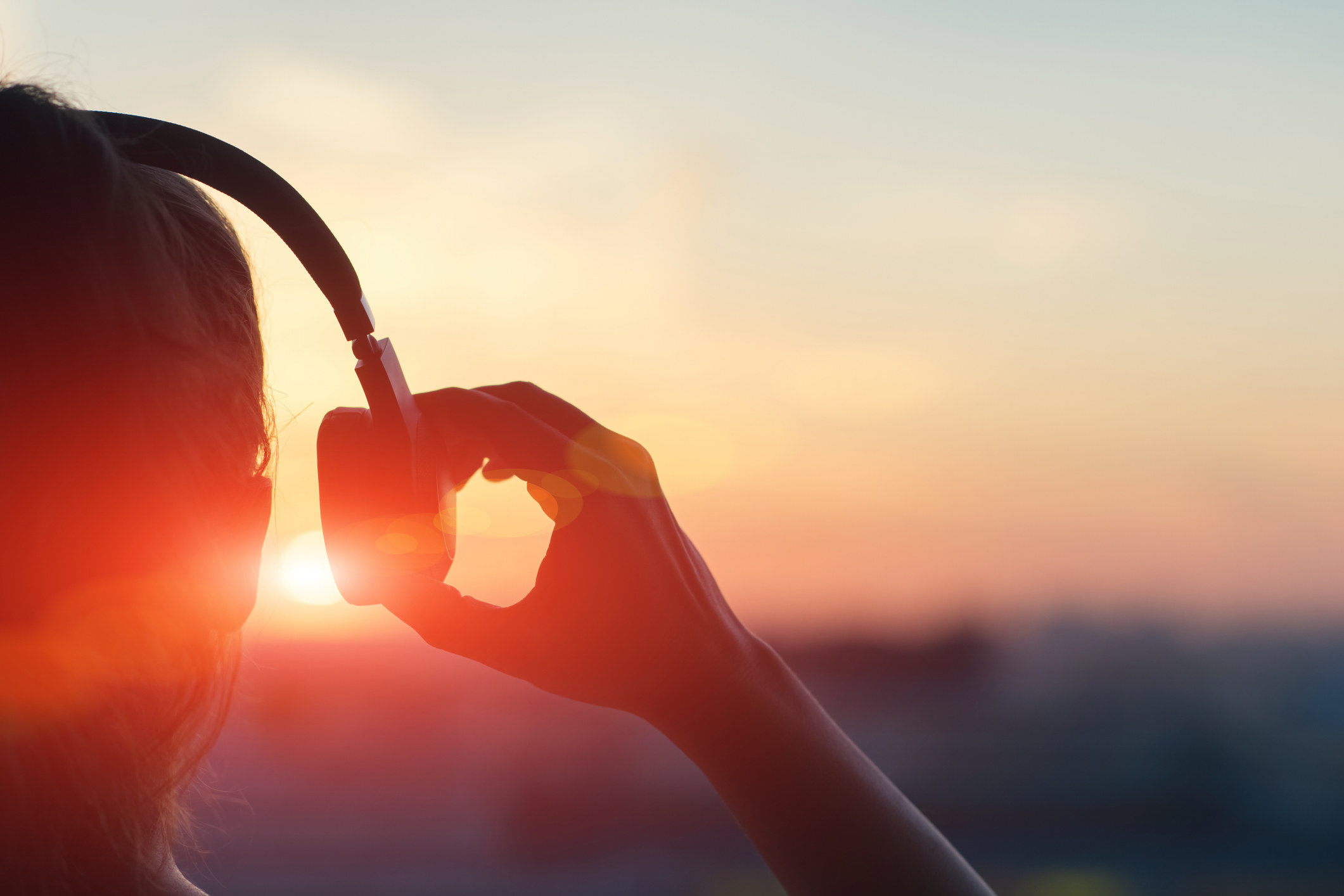 photo showing someone removing their over the head headphone with the sunset in the left corner