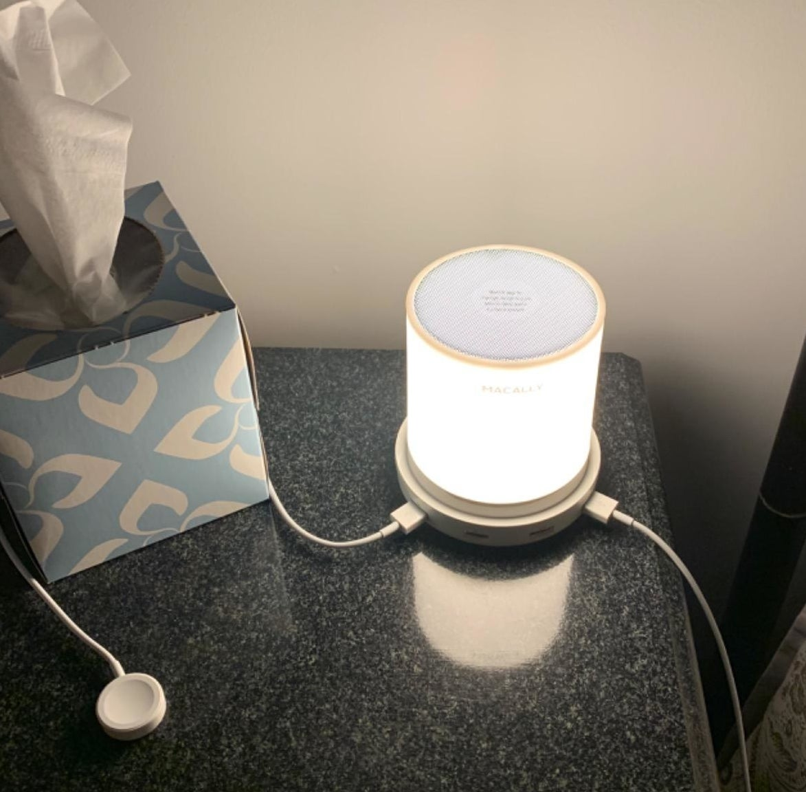 reviewer's lamp on a bedside table with a couple chargers plugged into it
