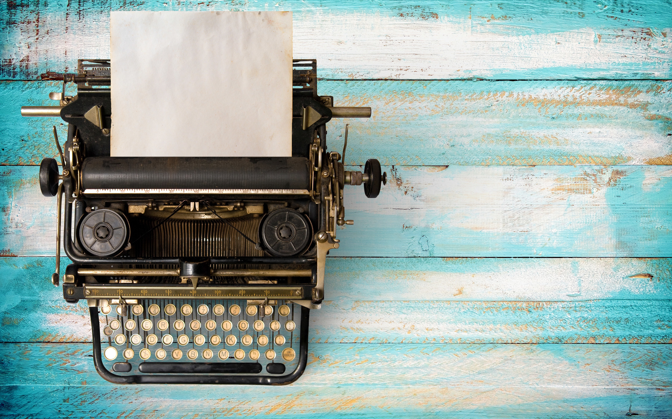 photo of a vintage typewriter with a black piece of paper, the typewriter is on top of a blue and white table