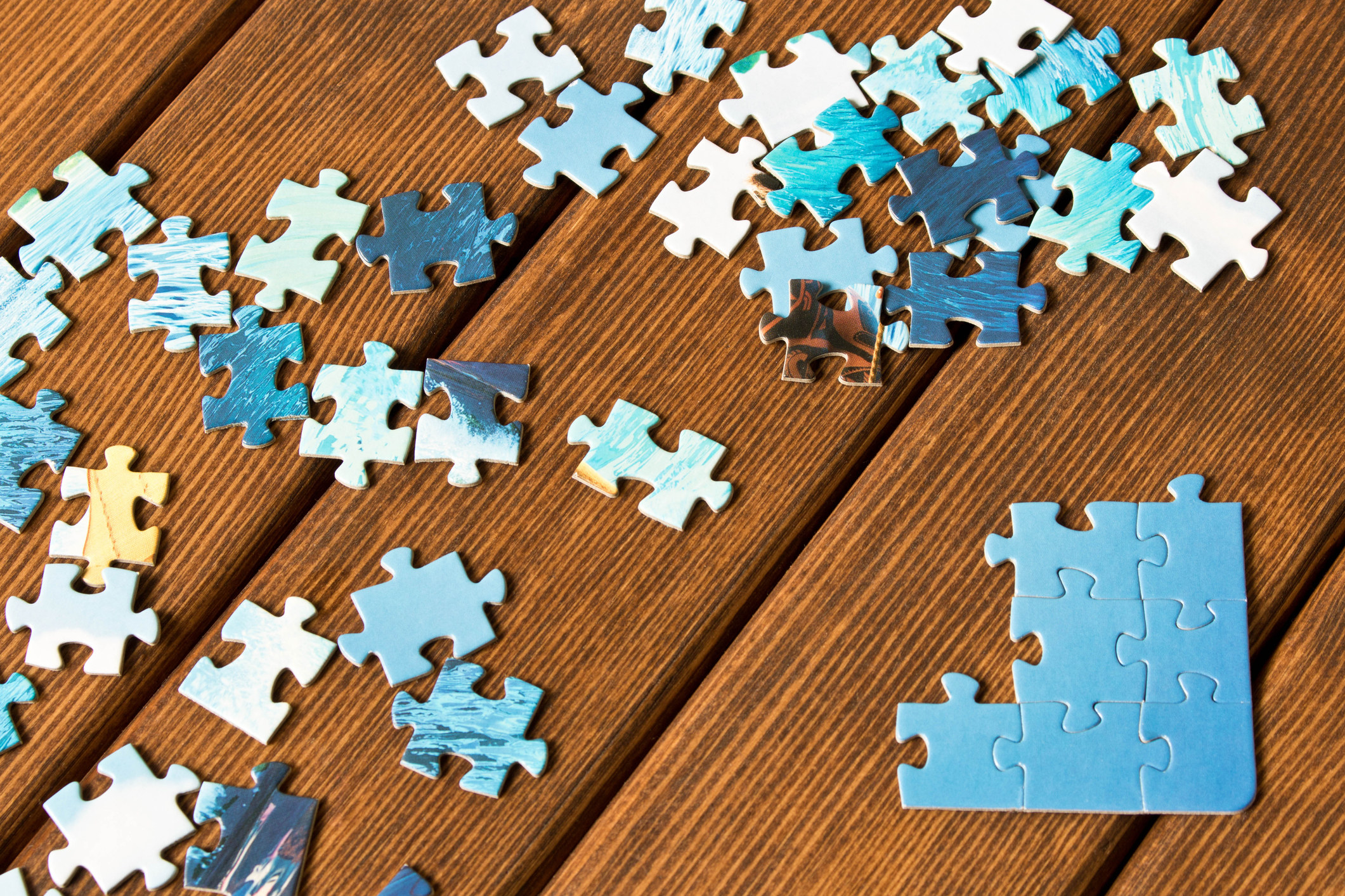 photo of a dissembled blue puzzle slowly being pieced together on top of a brown wooden table