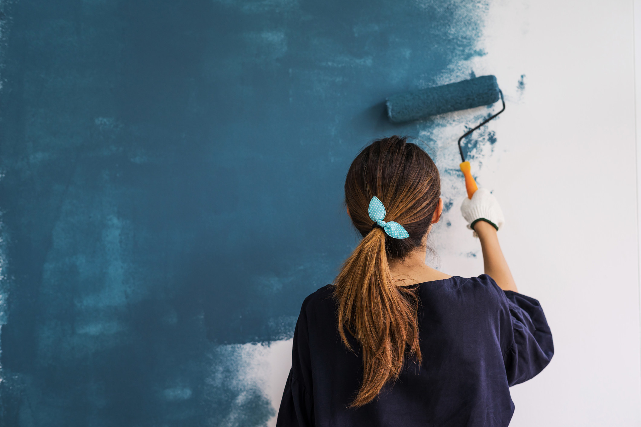 photo of a woman painting a wall with a blue hairband, the wall is being painted from a white to navy blue color