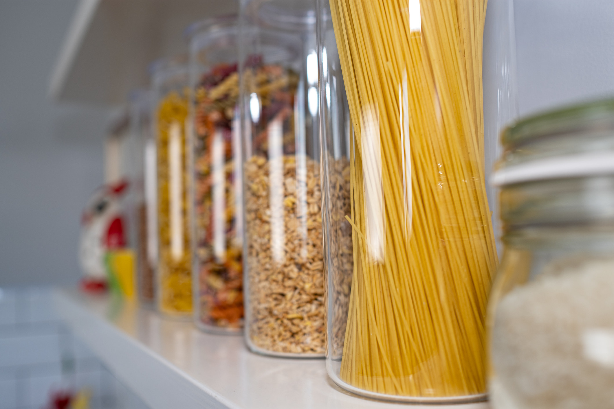 an image of pantry shelved items such as pasta, granola and other various snacks in glass containers